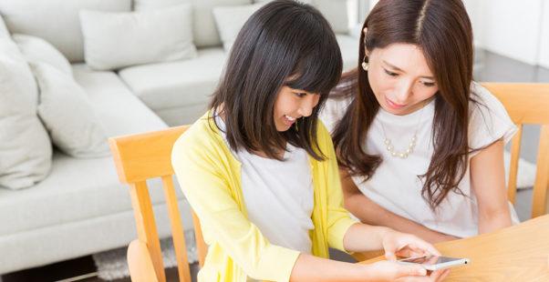 お母さんと一緒にスマホを見る小学生の女の子の写真