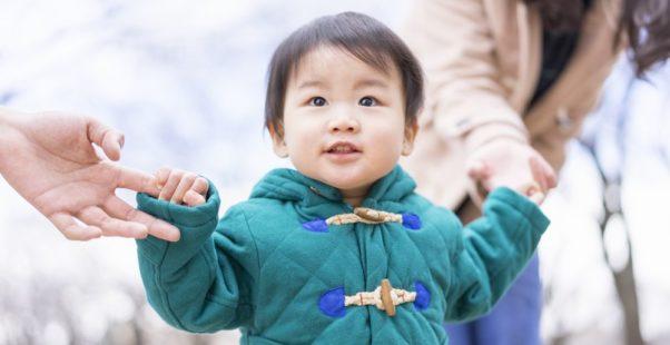両親と手をつなぐ幼い男の子の写真