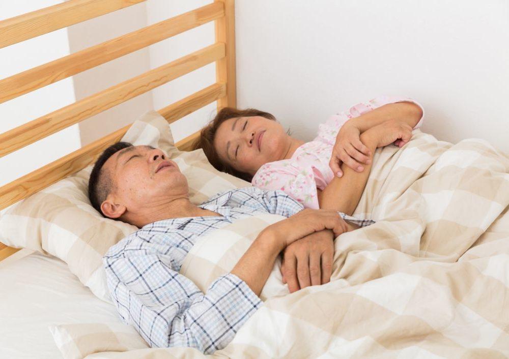 睡眠中の夫婦の写真