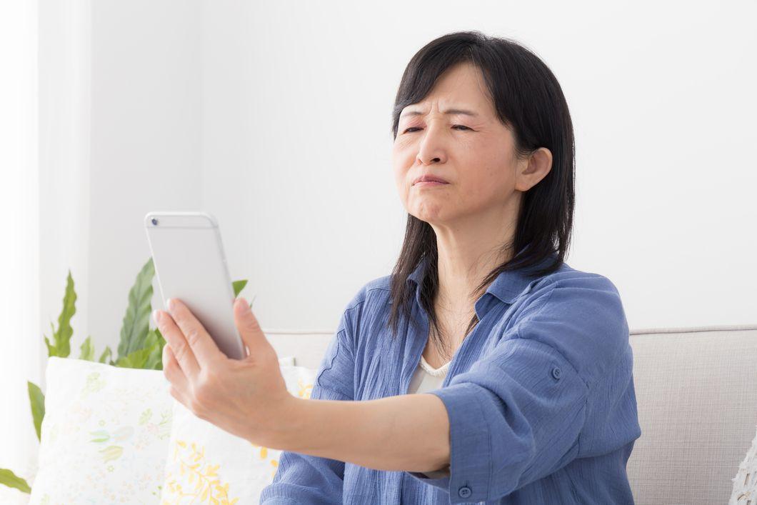 老眼でスマホの画面が見えにくい女性の写真