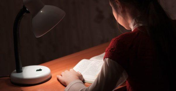 薄暗い部屋で本を読む子どもの写真