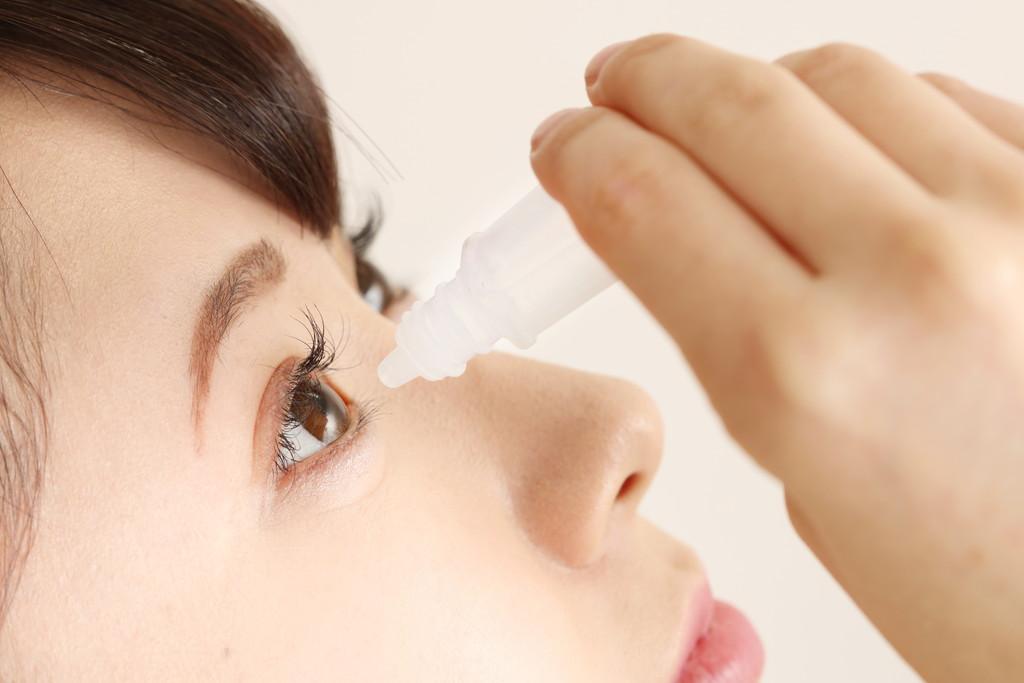 目薬をさす女性の写真
