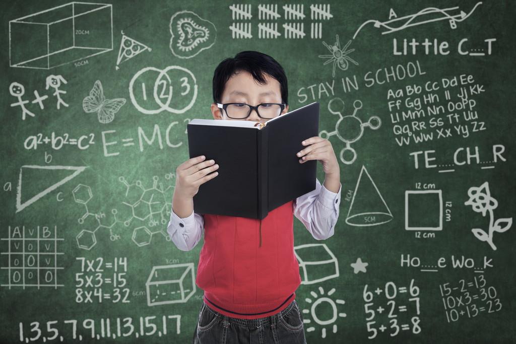 メガネをかけて本を読む男の子の写真