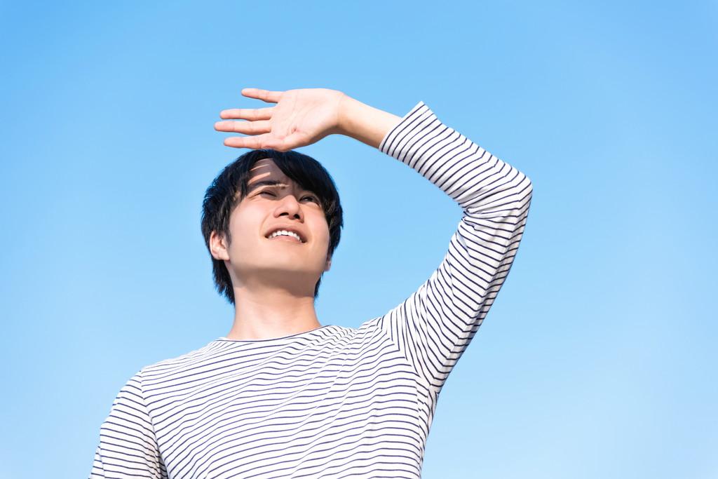 まぶしそうに空を見上げる男性の写真