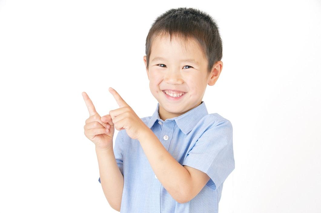 指をたてる笑顔の男の子の写真
