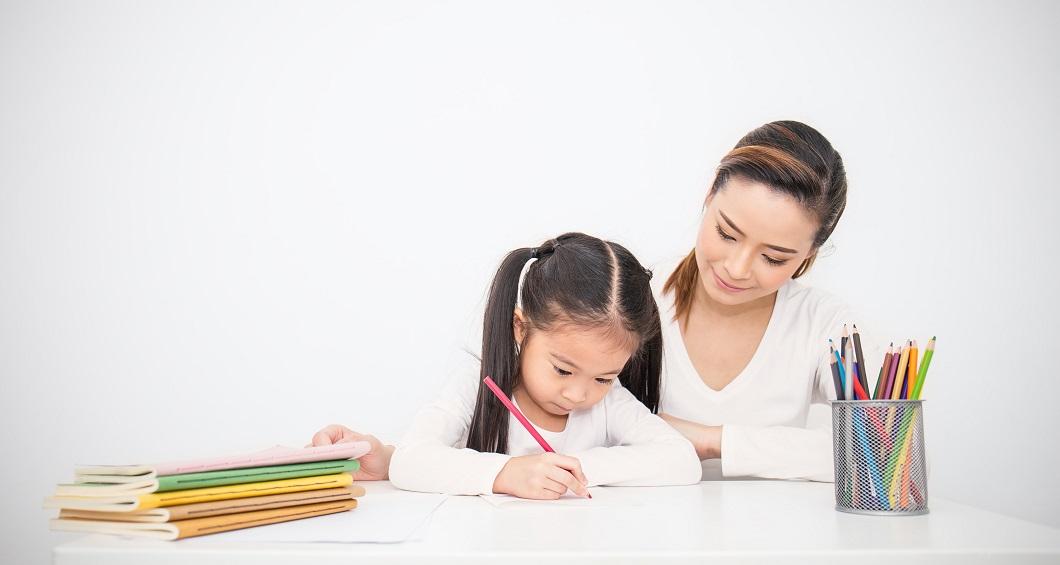 ママと一緒に何か描いている女の子の写真