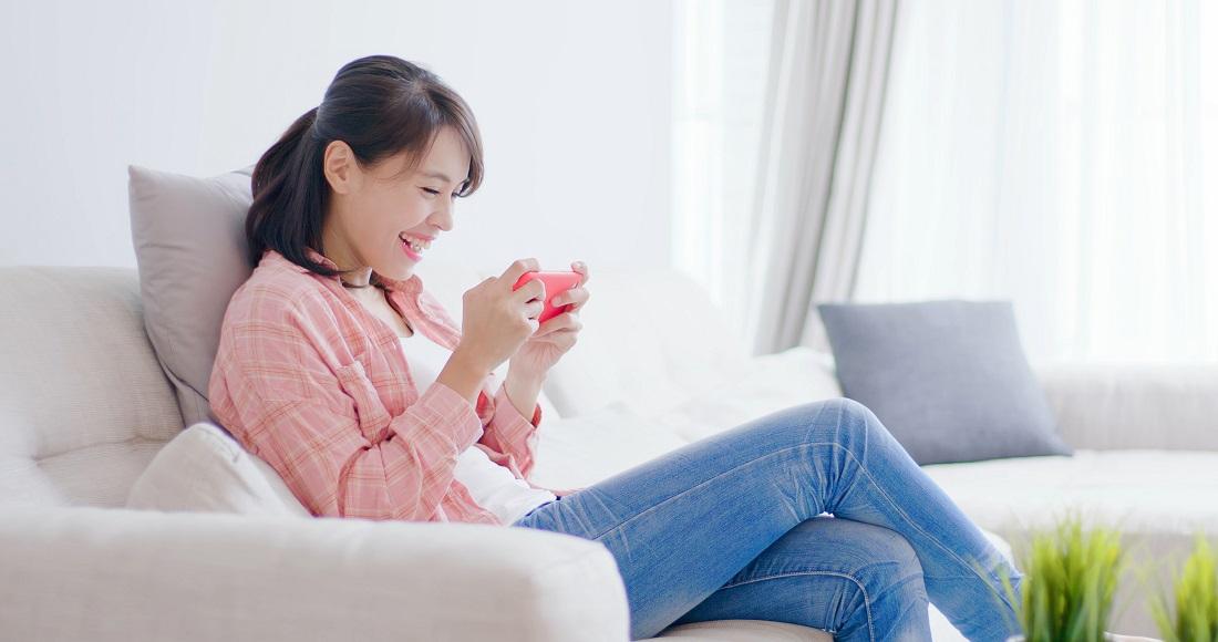 ソファに座ってゲームをする女性の写真