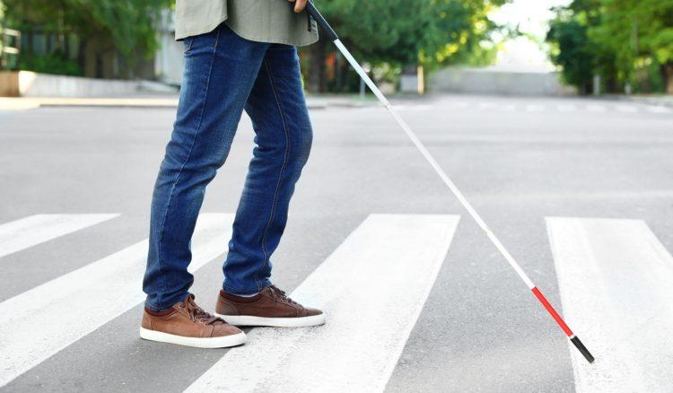 白杖をもって横断歩道を渡る視力障がいの男性