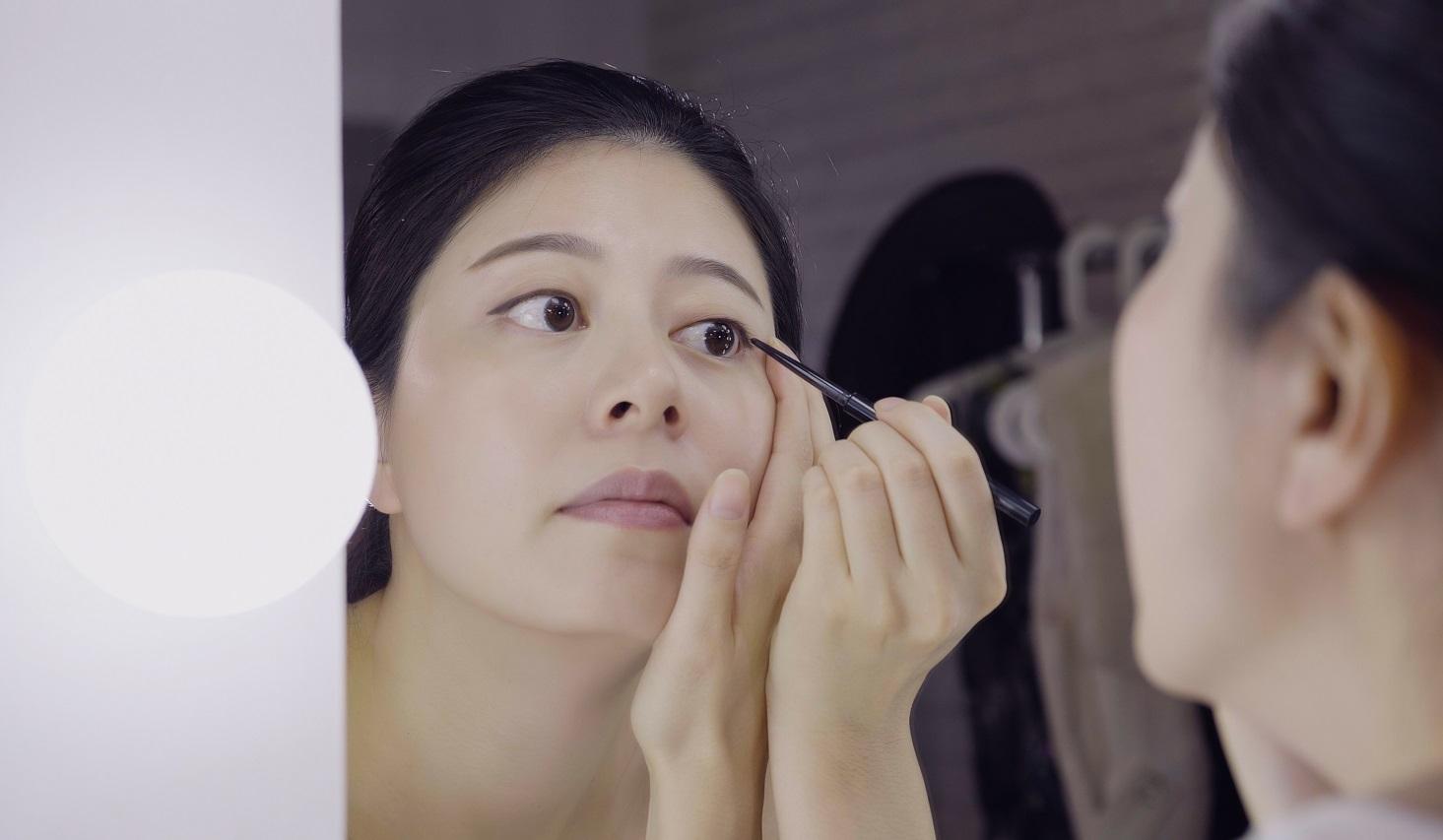 鏡を見ながら目の際にアイラインを入れる女性