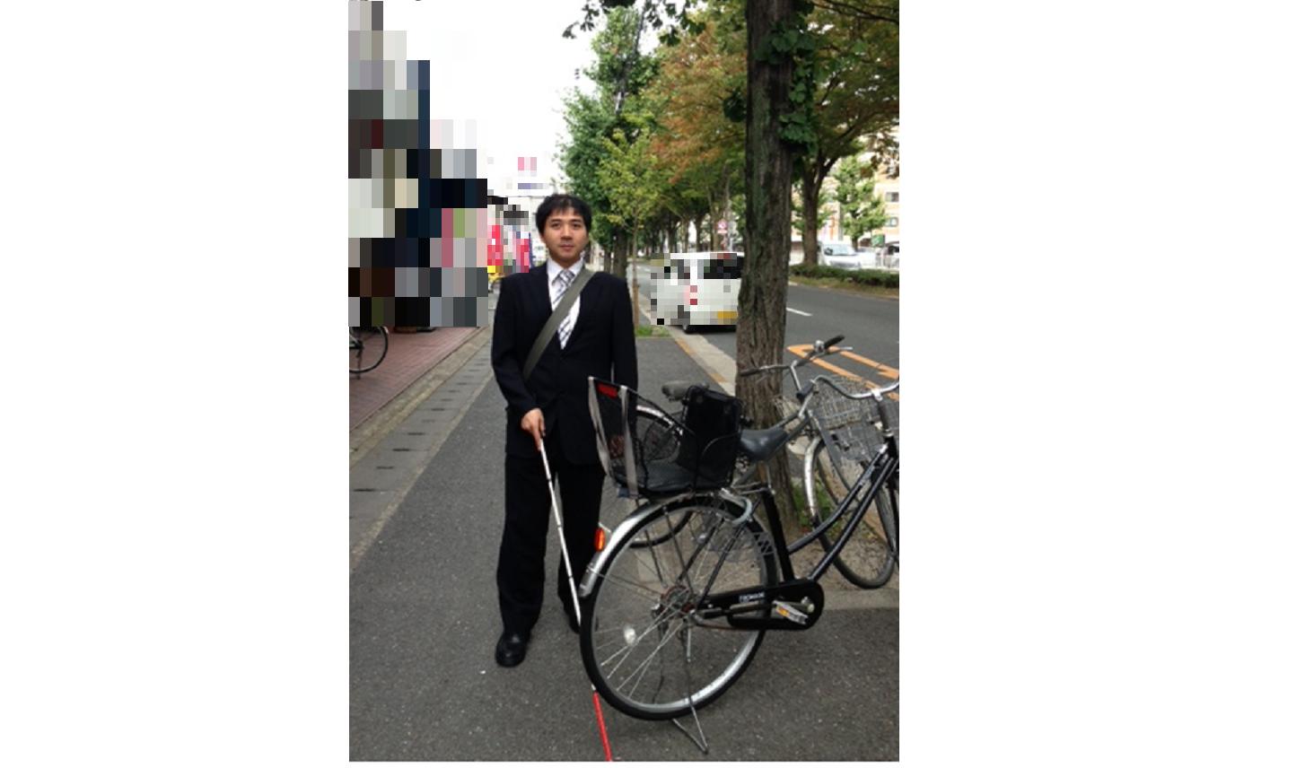 歩道に止めた自転車で通りづらい様子の視覚障がい者