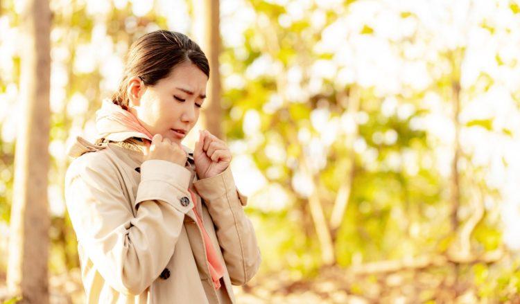 秋の自然の中にいて寒そうにしている女性