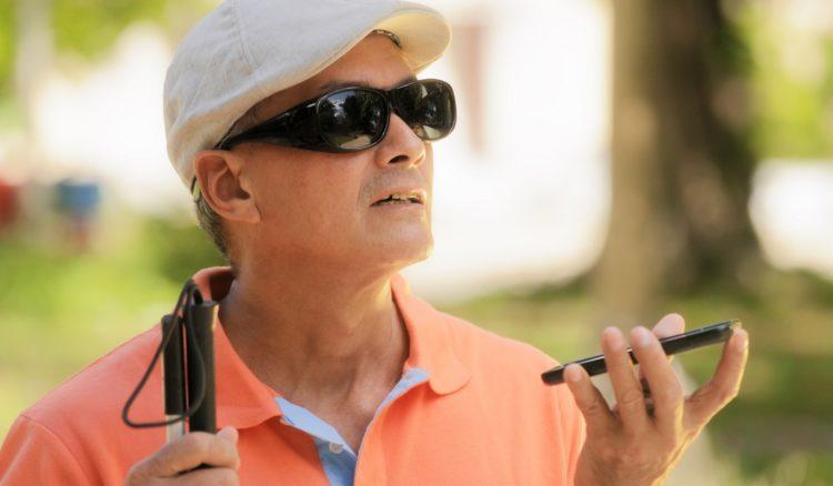 目の不自由な人が携帯の音声機能を使っている