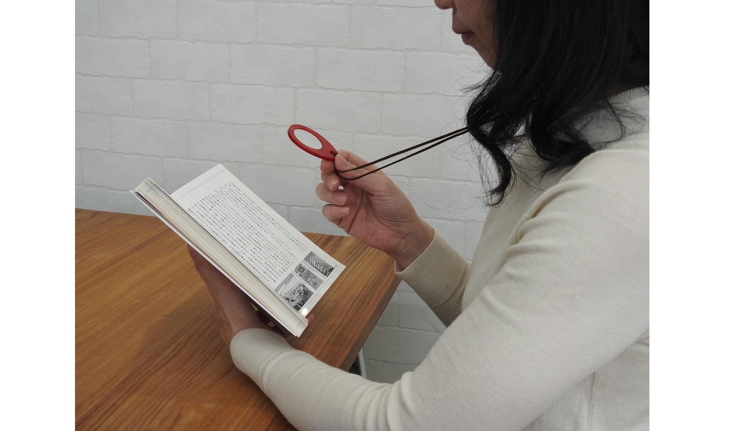 ルーペを使って本を読む女性