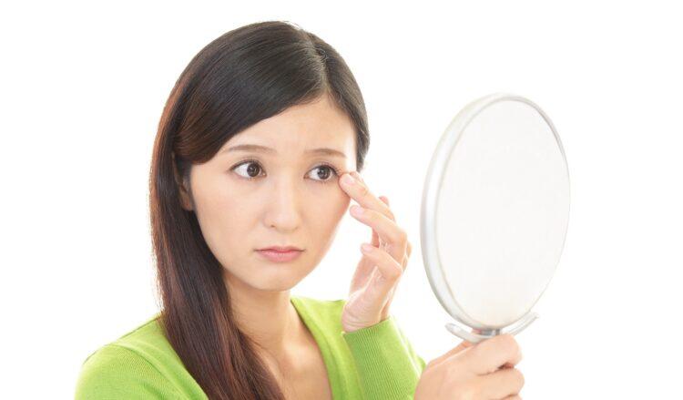 瞼のピクピクが気になって鏡をみる女性