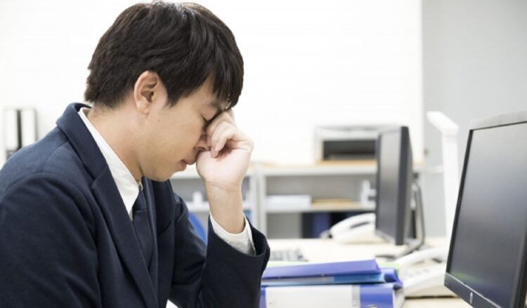 パソコン作業で疲れてた目を押さえる男性