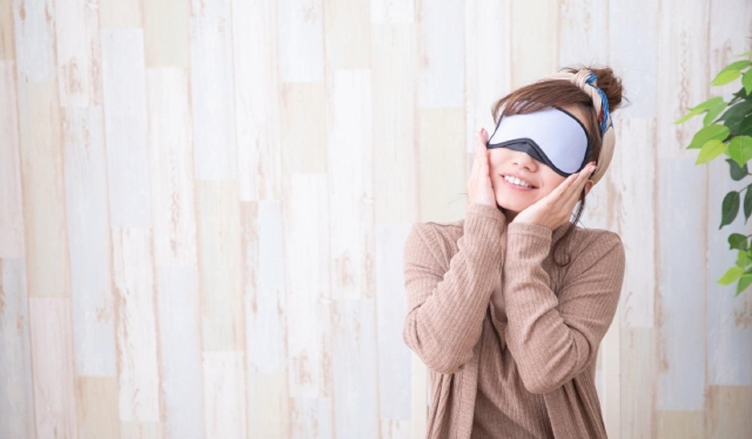 アイマスクで目を温めて疲れを和らげる女性