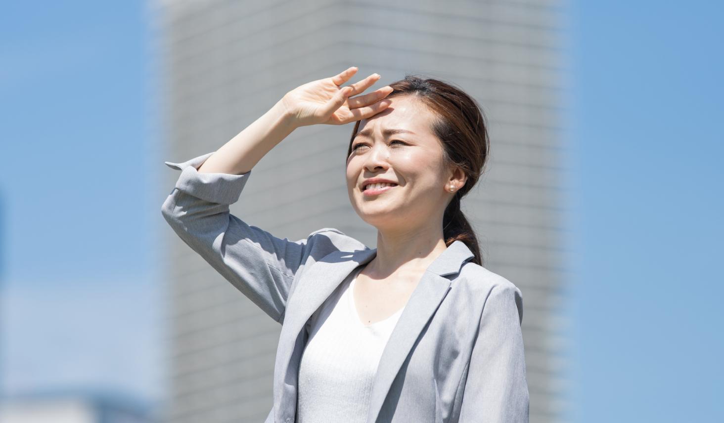 太陽の光を浴びて眩しそうに見上げる女性